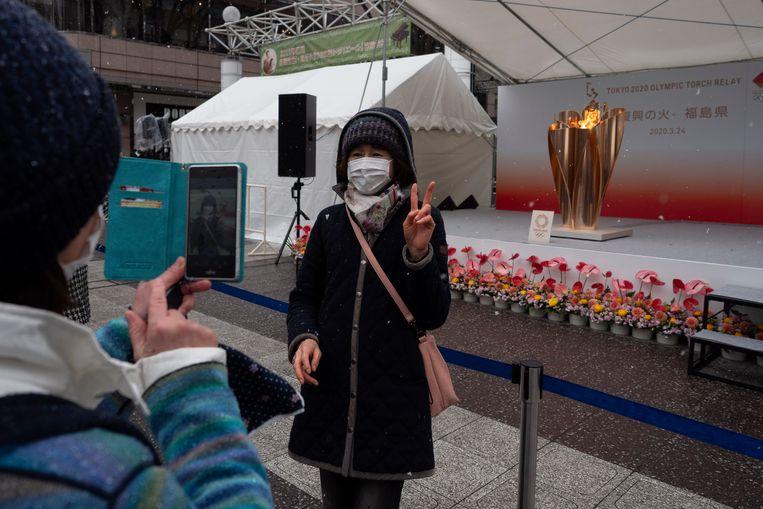 Een vrouw poseert met de Olympische vlam in de Japanse stad Fukushima. Beeld AP