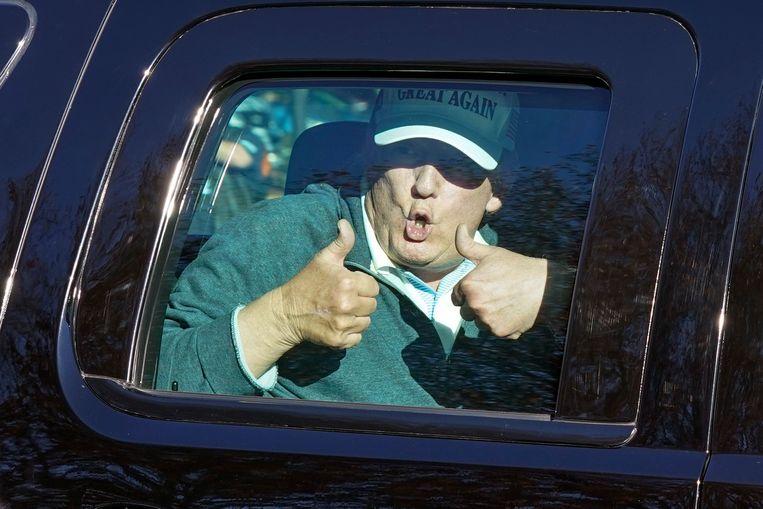 President Donald Trump steekt zijn duimen omhoog na een potje golf afgelopen zondag. Beeld AP