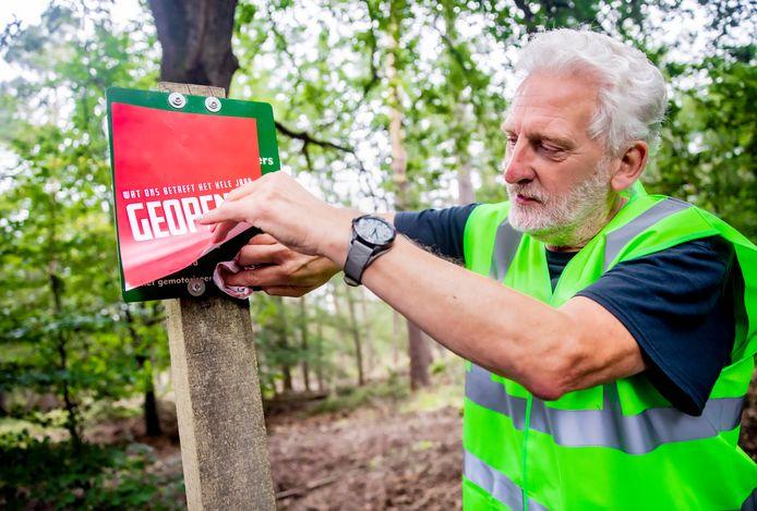 Harry Voss (Stichting Faunabeheer) maakt op Kroondomein Het Loo een bord schoon om het pamflet voor hun actie te kunnen ophangen.
