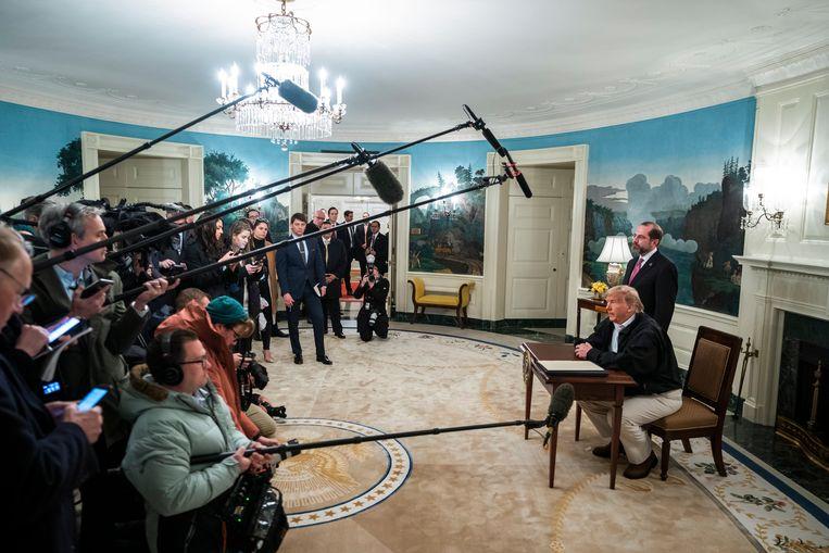 President Trump tekent, onder grote belangstelling, een steunpakket van 8,3 miljard dollar coronapakket.  Beeld EPA