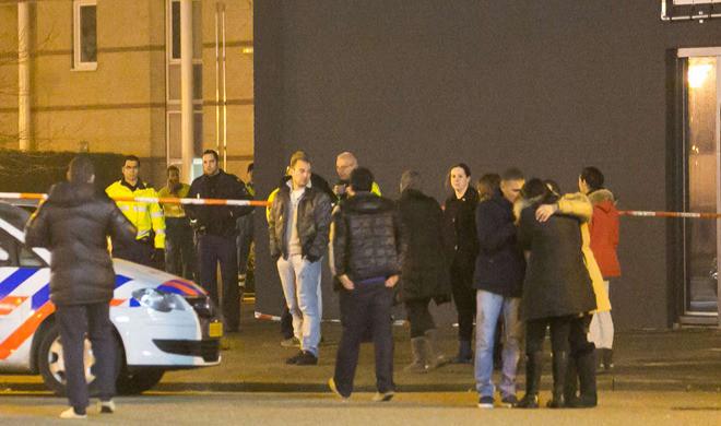 Bekenden van het slachtoffer en nieuwsgierigen maandagavond op de plek van de liquidatie.