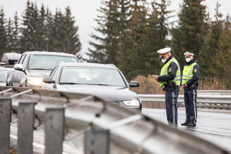 Politie-agenten controleren automobilisten in verband met de in Oostenrijk geldende reisrestricties. Beeld AFP