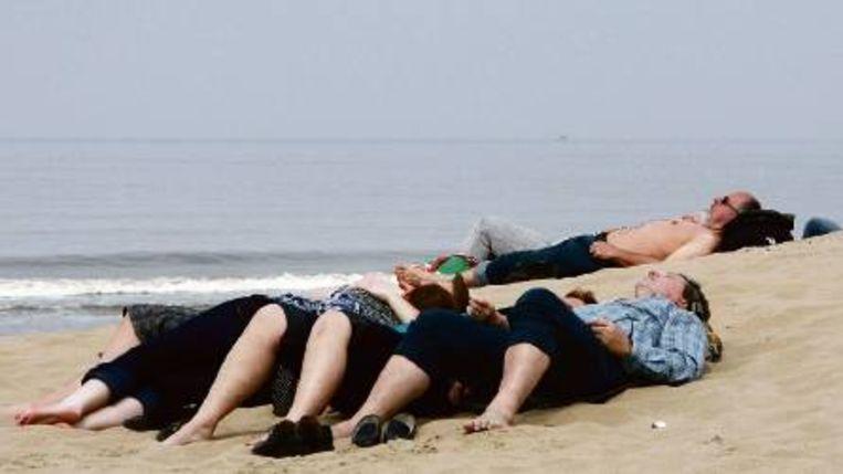 Strandgasten genieten van de voorjaarszon bij Zandvoort. ( FOTO ANP) Beeld