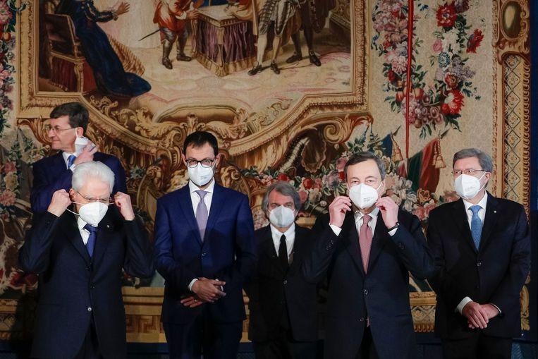 De Italiaanse president Sergio Mattarella (linksvoor) en premier Mario Draghi (tweede van rechts) na de beëdiging van de nieuwe regering.  Beeld AFP
