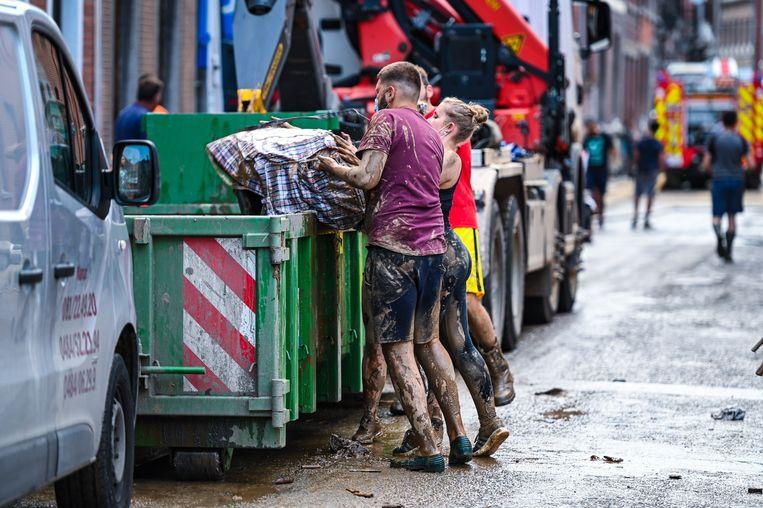 Inwoners van Bomel, bij Namen, ruimen puin na de overstroming van afgelopen weekend.  Beeld BELGA