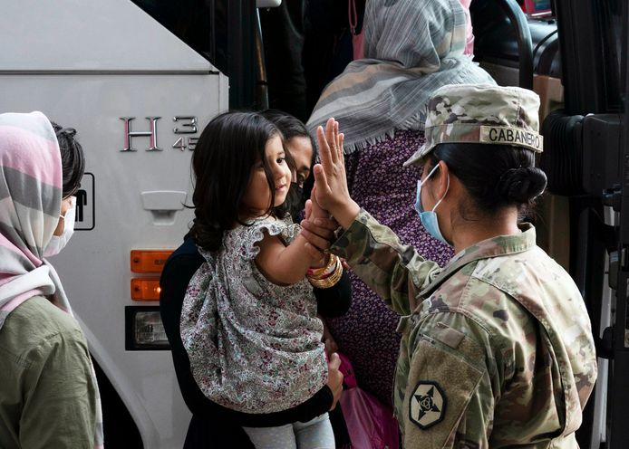 Een Amerikaanse soldaat geeft een high-five aan een Afghaans meisje uit Kaboel na geland te zijn op Dulles International Airport in Virginia.