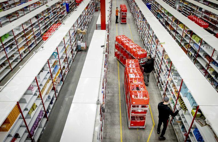 Medewerkers van online supermarkt Picnic in het distributiecentrum. Bezorgdiensten hebben het extra druk door de lockdown en de komende feestdagen.  Beeld ANP