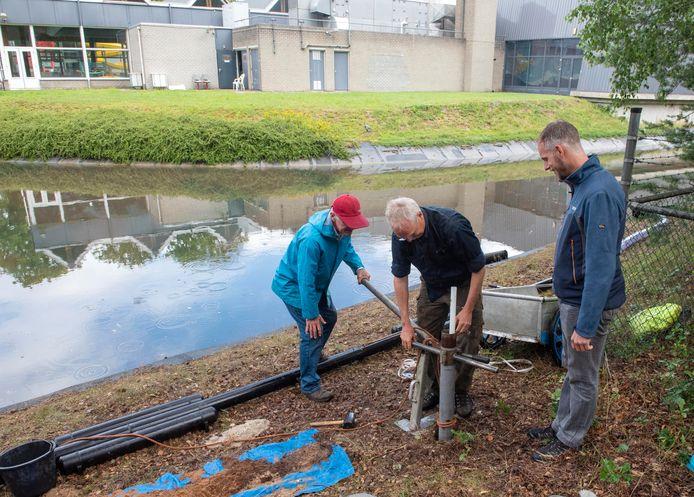 Karel Hanhart van het bedrijf Eelerwoude plaatst in opdracht van het waterschap Vallei en Veluwe peilbuizen bij de Kanovijver van Bosbad Putten, onder toeziend oog van Wim Zeeman van de Bekenstichting (l) en Christian Huising (r) van het waterschap.