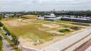 De opvallende, gele WRZV-hallen op de achtergrond, met in de verte de blauwe, oude WRZV-hallen. Het braakliggende terrein op de voorgrond is de plek waar Beers voorheen gevestigd was.