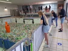 Zwemclub PFC Rheden vult oude zwembad De Dumpel bij wijze van afscheid met petflessen