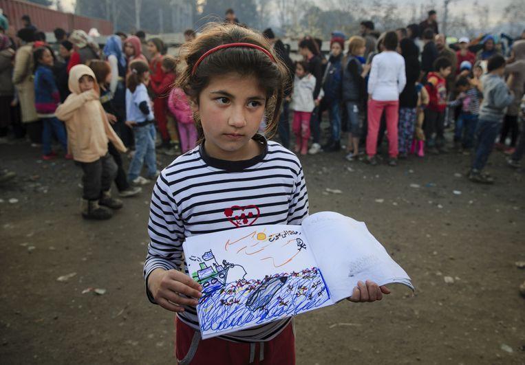 Een 9-jarig Syrisch meisje uit Aleppo toont een tekening waarop ze een reddingsactie van syrische vluchtelingen door de Griekse overheid afbeeldt. Beeld ap