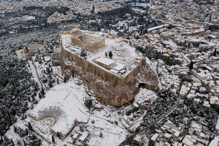 Zo heeft u Athene vermoedelijk nog nooit gezien, onder een sprookjesachtige laag sneeuw. In de Griekse bergen en het noorden van het land is sneeuw niets bijzonders, maar de hoofdstad heeft er veel minder vaak mee te maken.  Beeld AFP