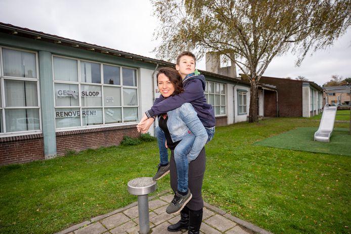 Kim Antonissen samen met haar autistische zoon Sijmen voor het pand waar vroeger de Sint Martinusschool was gevestigd.