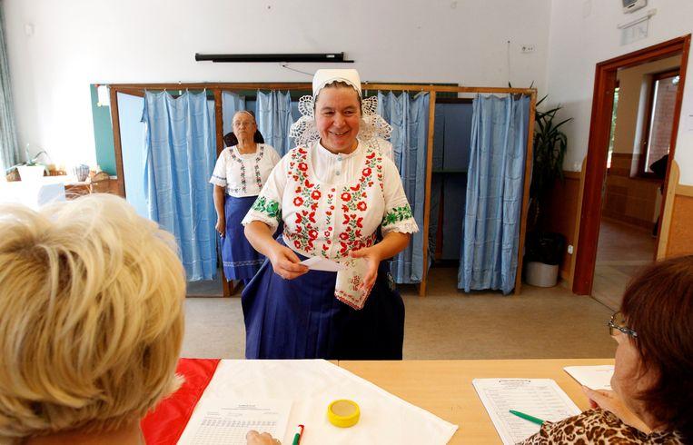 Een Hongaarse vrouw in traditionele klederdracht brengt haar stem uit in het referendum van gisteren. Beeld REUTERS