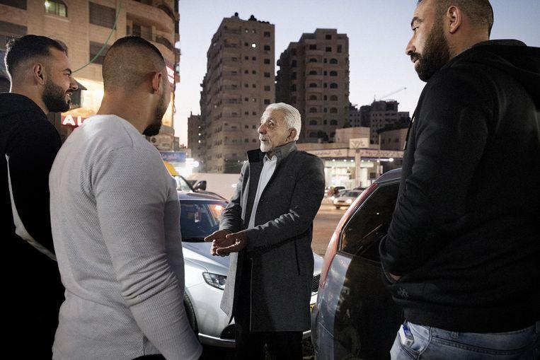 Gemeenschapsleider Mounir Abu Ashraf Zghayer (die in een straatje woont waar alle panden van hem en zijn broers of ooms zijn) praat met een groep jonge mensen.  Beeld Daniel Rosenthal