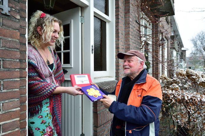 Patricia Lucas geeft in het kader van de lokale complimentenactie een doosje chocolade aan pakjesbezorger Martien van den Anker.