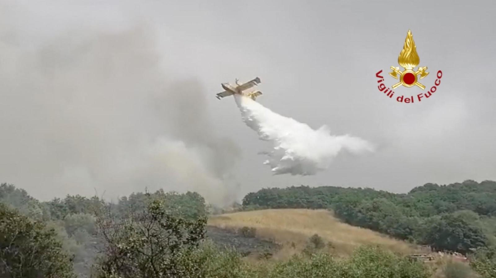 Een blusvliegtuig dumpt water op een bosbrand bij de stad Oristano.