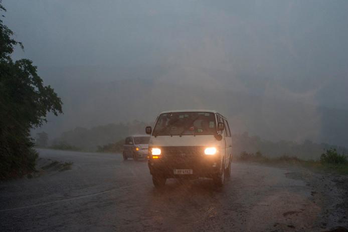 Auto's banen zich een weg door enorme regenval tijdens het begin van de tropische cycloon Idai.
