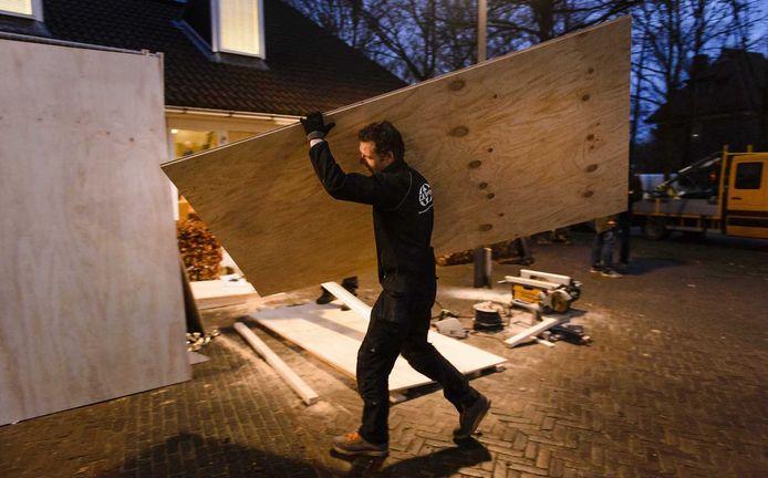 Bij het gemeentehuis van Geldermalsen wordt de schade gerepareerd, die is ontstaan nadat rellen uitbraken terwijl de raad bijeen was om een besluit te nemen over de komst van een azc.