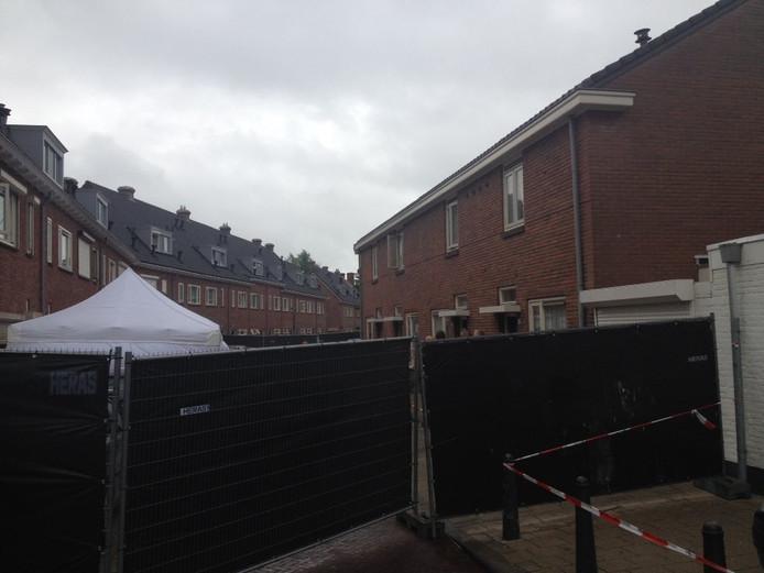 De huizen aan de Wilgenstraat die worden onderzocht zijn afgezet. Het lichaam van het slachtoffer is afgeschermd met een witte tent.