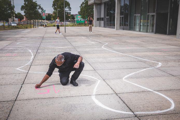 Kunstenaar Mo Shabini tekent op de grond voor het Gentse gerechtsgebouw.