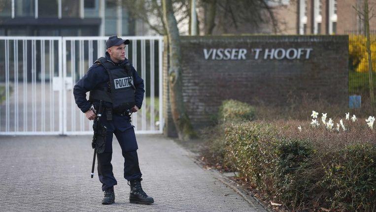 Een zwaarbewapende agent voor de gesloten poort van het Visser 't Hooft lyceum in Leiden. Beeld EPA