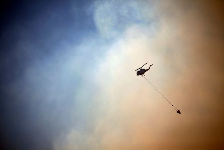 A helicopter drops water on a fire approaching homes near the Blue Mountains suburb of Blackheath, located around 70 km (43 miles) west of Sydney, October 23, 2013. A state of emergency has been declared in the Australian state of New South Wales, as bushfires continue to burn west of Sydney and weather conditions expected to worsen over the coming days. Around 60 fires are still burning across the state. REUTERS/David Gray     (AUSTRALIA - Tags: DISASTER ENVIRONMENT TPX IMAGES OF THE DAY) Beeld REUTERS