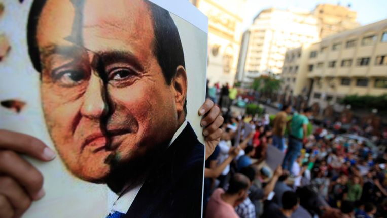 Demonstranten laten een gebroken foto zien met links het gezicht van Mubarak en rechts dat van legerchef al-Sisi, die recent de verkiezingen heeft gewonnen. Beeld REUTERS
