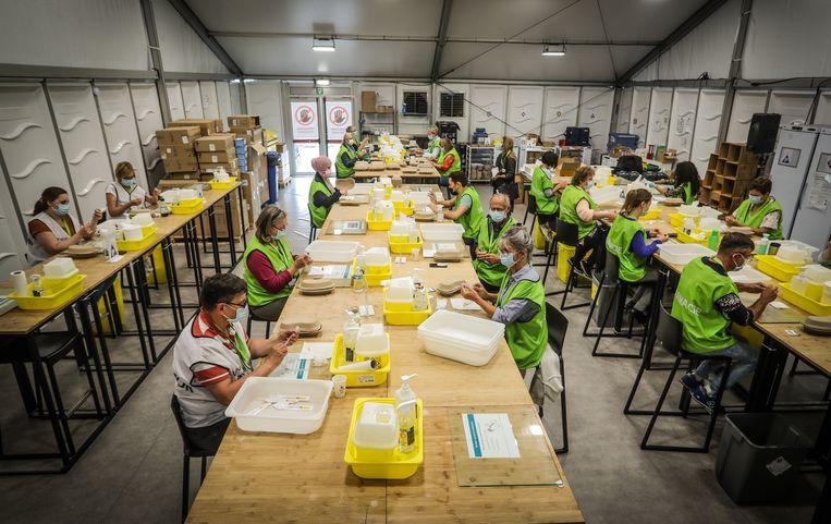 Medewerkers in het vaccinatiecentrum van Antwerpen op Spoor Oost bereiden nog elke dag duizenden prikken voor. Beeld Pieter-Jan Vanstockstraeten / Photo News