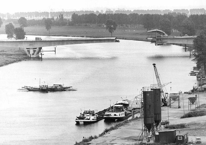 De brug in de rijksweg A50 over de Maas is in aanbouw. In het midden nog de veerpont Ravenstein - Niftrik (augustus 1974)