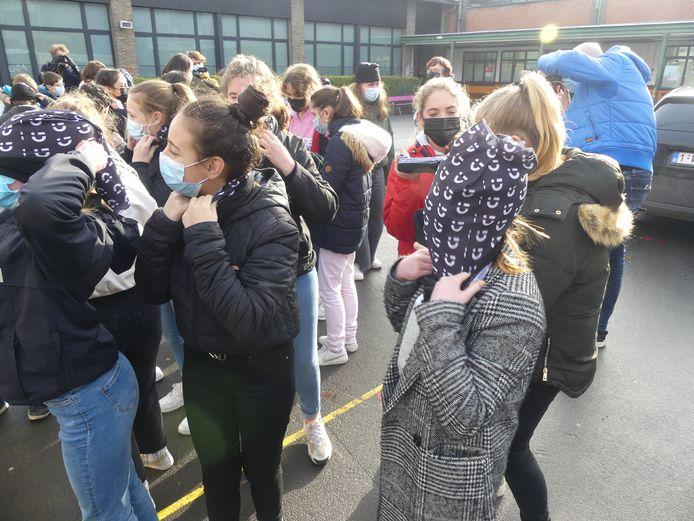 De leerlingen trokken allemaal een nekwarmer over hun hoofd.