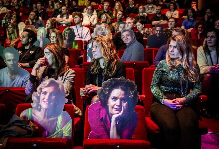 Bezoekers van een theatervoorstelling zitten op veilige afstand van elkaar, met kartonnen figuren ertussen. Beeld ANP