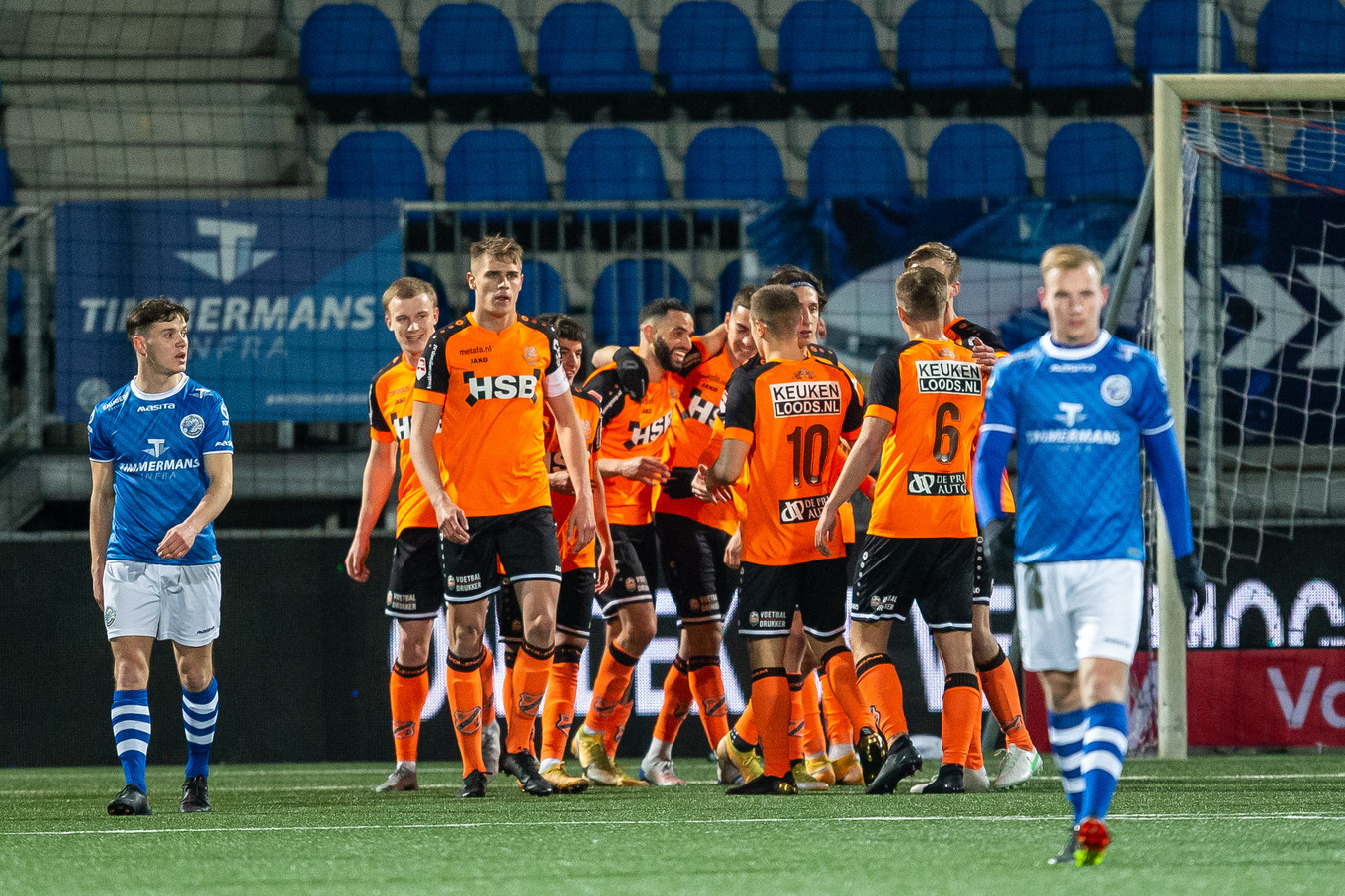 Terwijl de FC Den Bosch-spelers Jorn van Hedel (links) en Romano Postema (rechts) balen, vieren de spelers van FC Volendam een van hun vijf doelpunten.