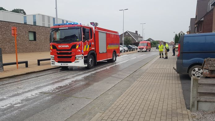 De brandweer spuit het wegdek schoon nadat een landbouwer zo'n 200 vloeibare mest verloor in Aartrijke. Ook de landbouwer helpt mee poetsen met een trekker.