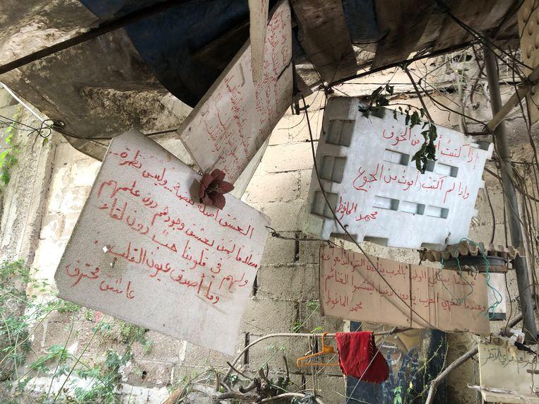 Abu Fadi heeft met viltstift Arabische gedichten op de borden geschreven van bekende dichters, zoals de Syrische Mohammed al-Maghout: 'Als ik schrijf, ga ik dood van de angst; als ik niet schrijf, ga ik dood van de honger'. Beeld Paulien Bakker