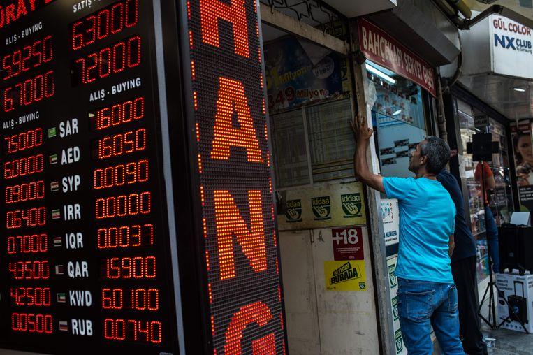 Mensen checken de wisseltarieven bij een wisselkantoor in Istanbul.  Beeld AFP