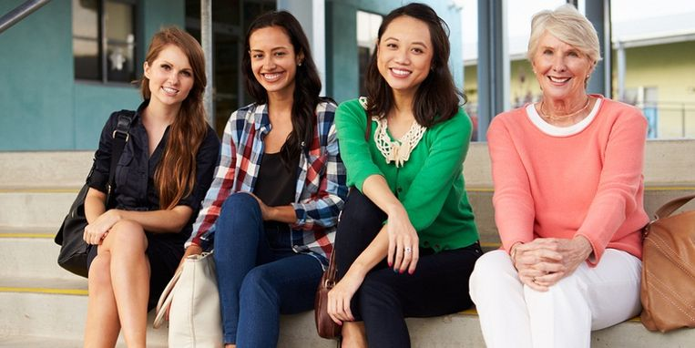 four-female-teachers-sitting-on-steps-at-entrance-of-school.jpg