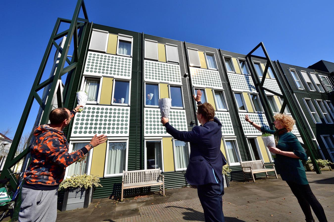 Bloemenactie voor bewoners van het Nieuwe ABG. Vlnr: Daan Kagchelland, diaken Anton Janssen en locatiemanager Marita Pieters.
