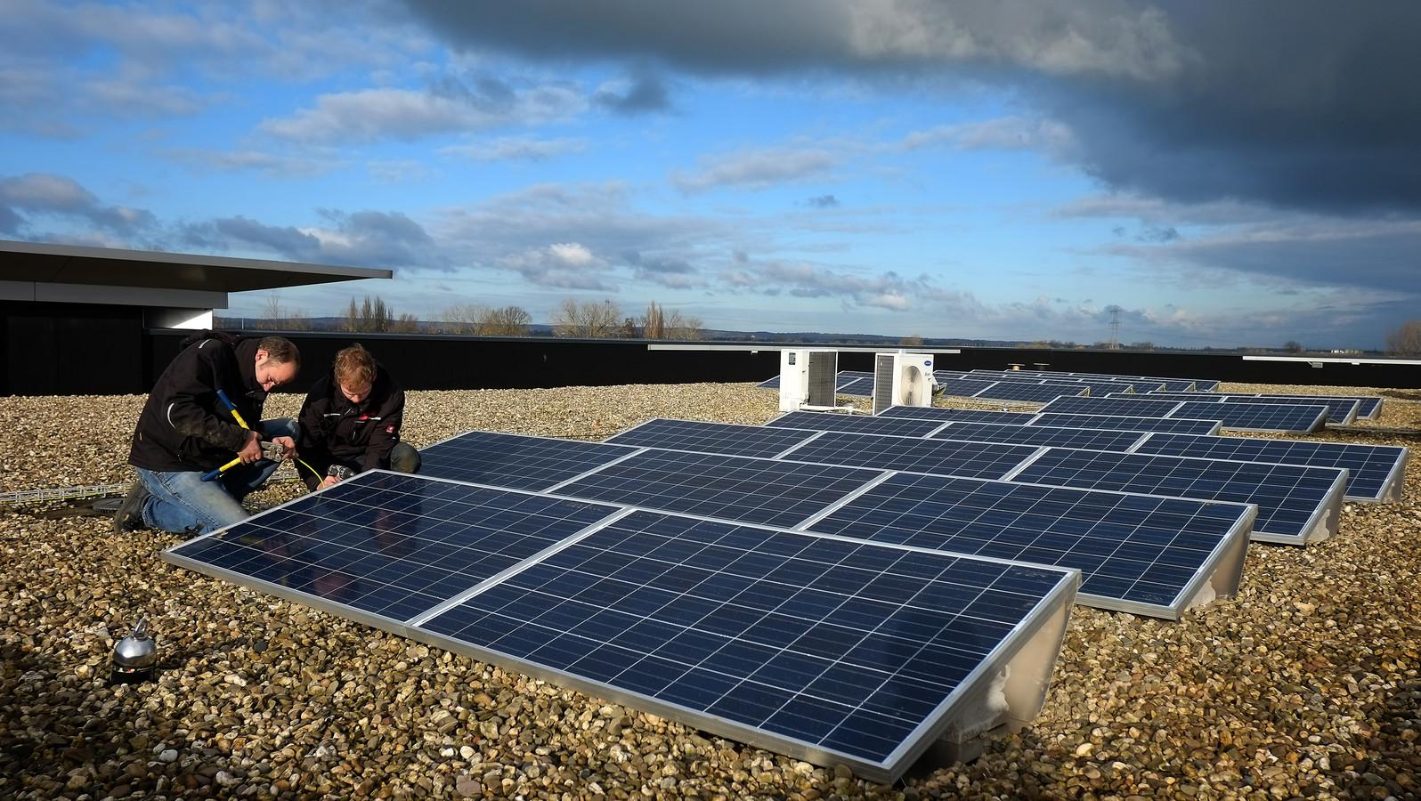 Zonnepanelen  worden aangebracht op het dak van een bedrijf.  Foto ter illustratie.