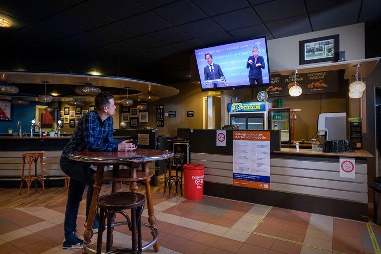 Voorzitter Rogier Schultz van de Utrechtse voetbalvereniging Elinkwijk kijkt naar de persconferentie van Mark Rutte. Beeld Werry Crone