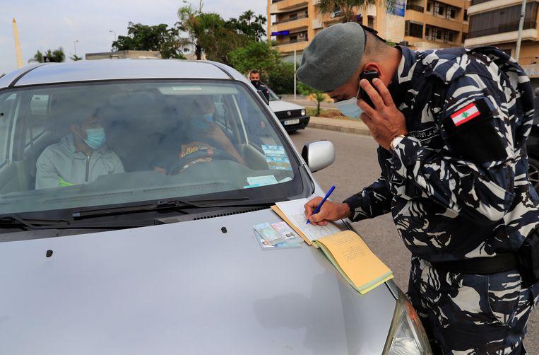 Op de bon: in Beiroet mogen auto's nu alleen om de dag de weg op. Dat hang af van het nummerbord, even of oneven. Beeld Hussein Malla / AP