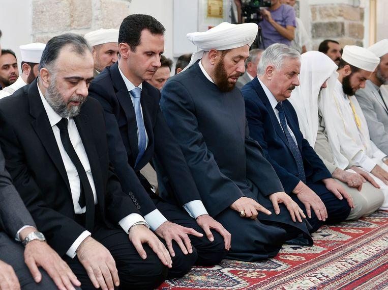 De Syrische president Bashar Assad heeft de afgelopen jaren meerdere gifgasaanvallen laten uitvoeren op zijn eigen bevolking. Hier bidt hij in een moskee in de stad Hama tijdens het suikerfeest, zondag. Beeld EPA