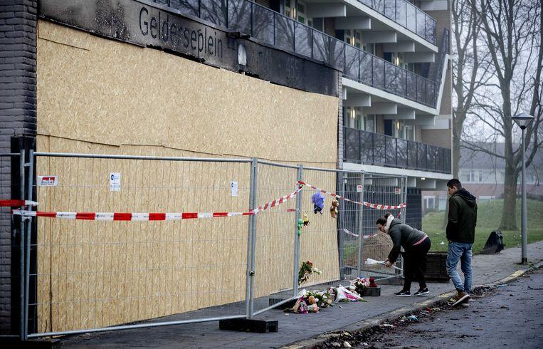 Bloemen en knuffels bij de Arnhemse flat waar een 39-jarige vader en zijn 4-jarige zoon om het leven kwamen.  Beeld ANP