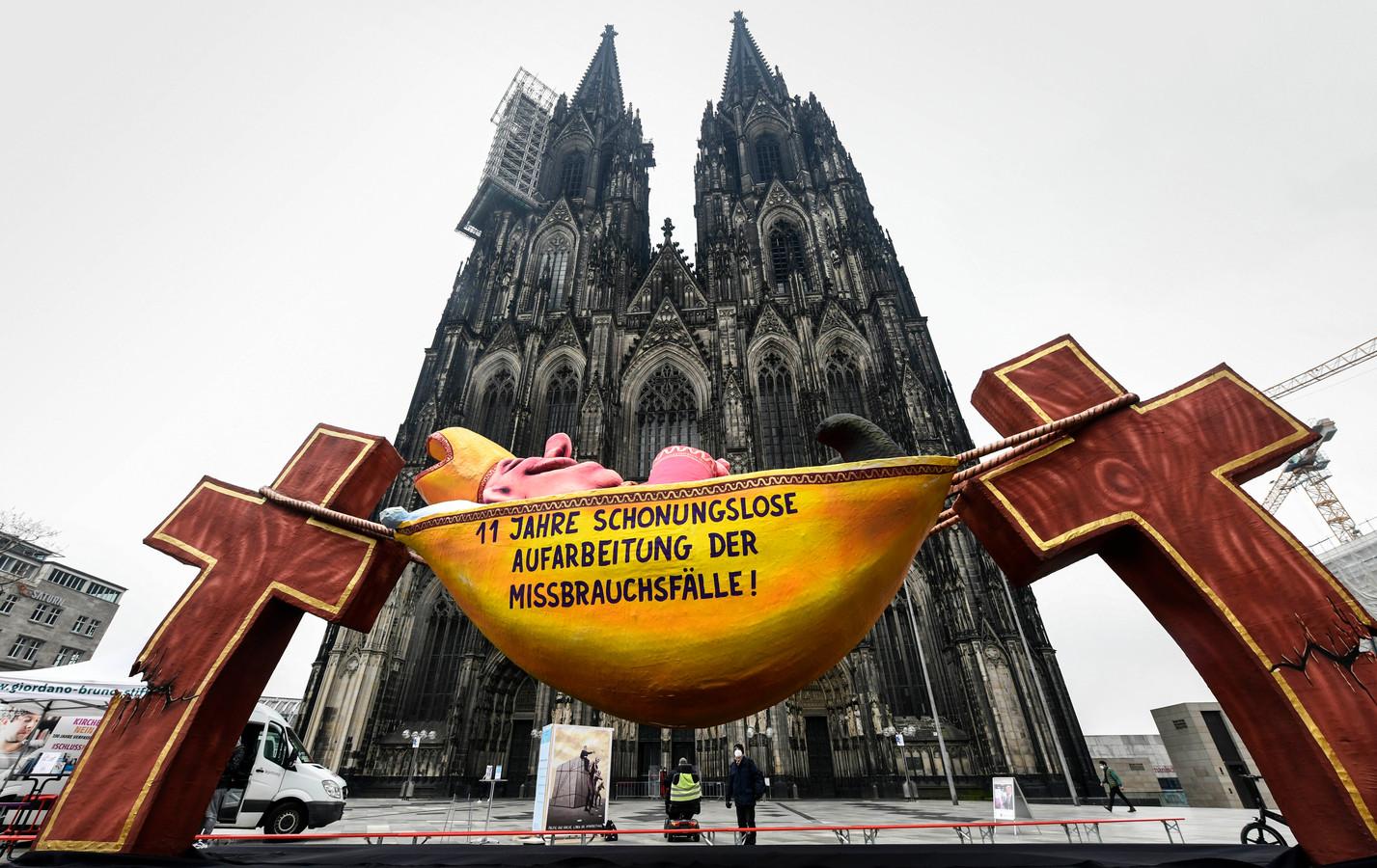 Een carnavalswagen met een afbeelding van een slapende kardinaal en de tekst '11 jaar meedogenloze afhandeling van misbruikgevallen' voor de Dom van Keulen op de dag van de publicatie van het onderzoeksrapport.