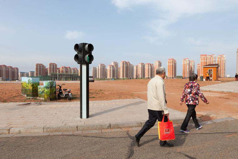 Passanten in Ordos passeren een nieuwe lege woonwijk. Beeld Ruben Lundgren