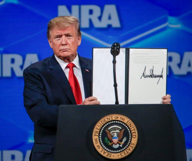 Tot verrassing van de NRA-leden toonde Trump een presidentieel bevel waarmee het wapenverdrag wordt opgezegd. Beeld EPA