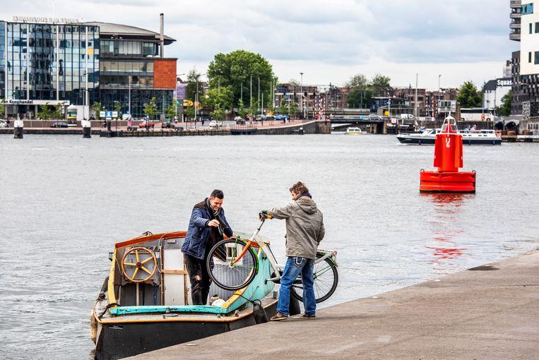 Een gestrande fietser wordt door een vriend over het IJ gevaren in Amsterdam-Noord.   Beeld Raymond Rutting / de Volkskrant