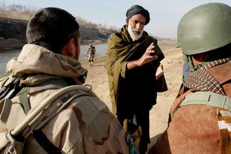 Militairen van een Nederlandse eenheid in Uruzgan spreken een man tijdens een patrouille in 2008. Beeld Hollandse Hoogte /  ANP