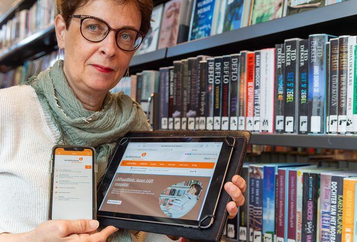 Directeur Hetty van de Weg laat de app zien die Bibliotheek Noord-Veluwe heeft ontwikkeld. Met die app zijn de activiteiten van de bieb tijdens de lockdown net zo toegankelijk als in normale tijden.