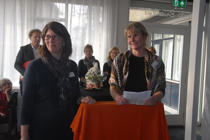 Vrijwilliger Mieke van Heugten en penningmeester Monique van den Broek, kort voor de onthulling van een sponsorbord.